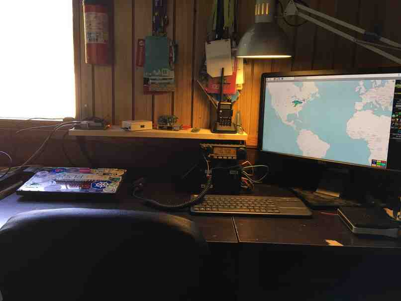 desk with computer screen, raspberry pis and a Yaesu FT-2900R and Baofeng UV-5R 2 meter amateur radios